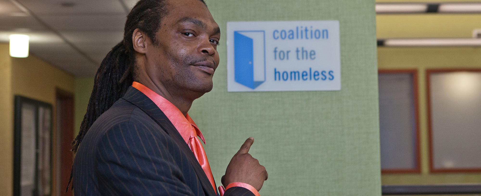 Man in suit points to sign featuring the Coalition for the Homeless logo.