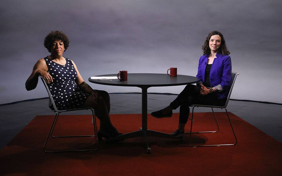 Two women seated facing each other at a round table in a television studio. CUNY TV's Sheryl McCarthy on the left and Coalition for the Homeless Policy Director Giselle Routhier on the right.