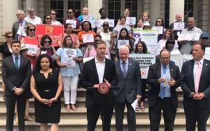 State Assemblyman Andrew Hevesi, other elected officials, and advocates stand on the steps of City Hall to urge Gov. Andrew Cuomo to sign legislation providing safe shelters for survivors of human trafficking into law.