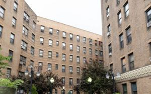 A large brick apartment building in Crown Heights, Brooklyn, with trees in the front.