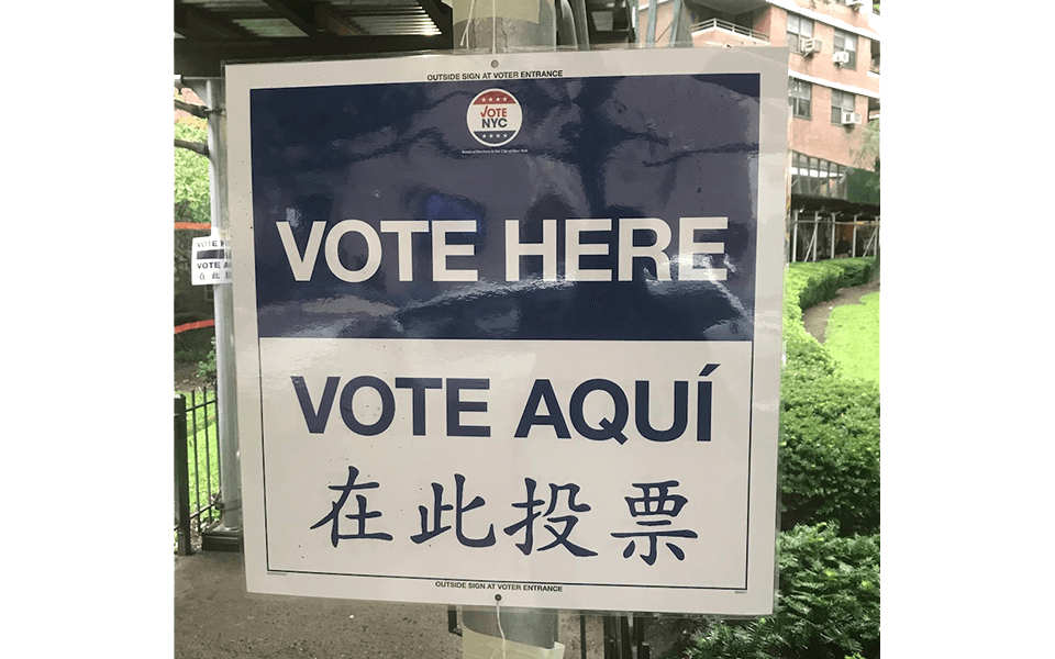 "Polling location sign. Text reads ""Vote here"" in English, Spanish, and Chinese"