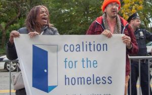 Two people hold a Coalition for the Homeless banner and chant at a rally.