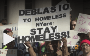 """Protesters holding signs saying: """"De Blasio to Homeless NYers: Stay Homeless!"""""""