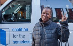 A woman in a coat holds up a peace sign in front of a Coalition for the Homeless food van.
