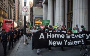"""People marching in lower Manhattan holding a banner reading: """"A Home for Every New Yorker"""""""