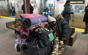 A man sits on a subway platform surrounded by bags.