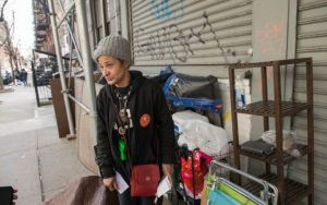 A homeless woman stands on the sidewalk near her belongings.
