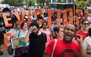 "A group of people march down the street holding signs that read ""EVICTION."""