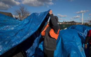 A man sets up a blue tarp as a tent.