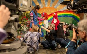 The cast of Sesame Street hold puppets as a camera films them