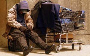 A man sleeping on the sidewalk next to a shopping cart.